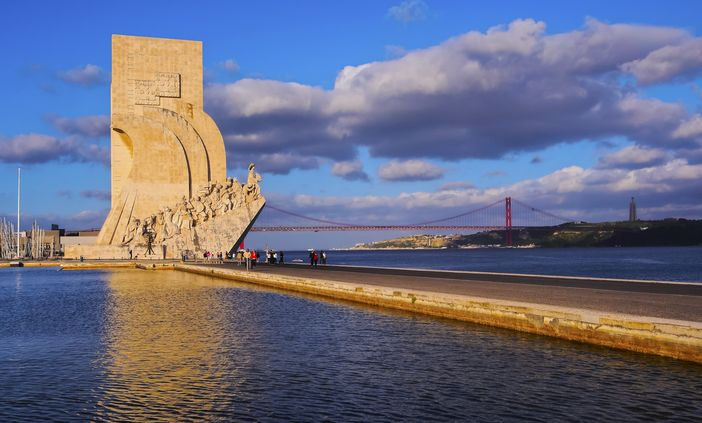 Cruise the Mediterranean: Monument to the Discoveries with the 25 de Abril Bridge in the distance