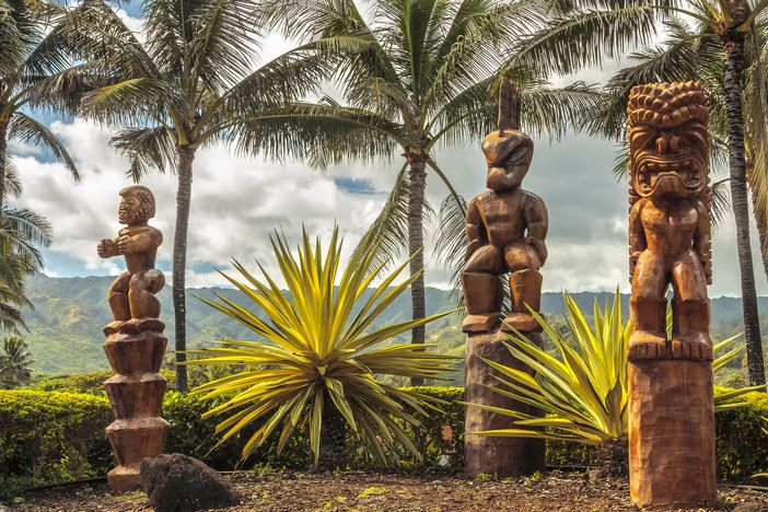 Hawaiian style tiki carvings with a beautiful hawaii scenery in the background