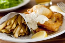 Crispy fish and chips dinner served with lemon wedge
