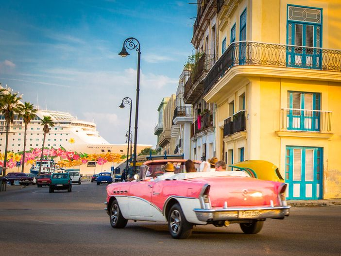 Typical Cuban vintage car and Norwegian Sky ship in the background