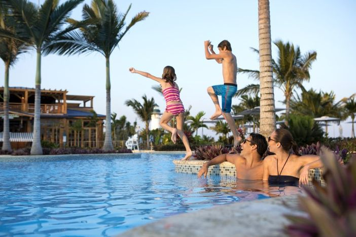 Family in the pool of Harvest Caye private island resort